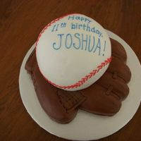 Baseball Glove And Baseball Buttercream baseball and buttercream baseball glove. The webbing and lacing on the glove are fondant.