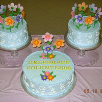 Volunteer Reception Cake WASC w/raspberry filling iced in whipped icing. Flowers are made from fondant/gumpaste mix.