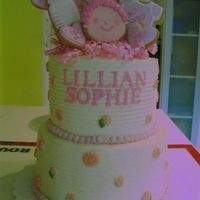 Christening Cake For Lillian top tier is lemon chiffon cake filled with raspberry puree, bottom tier is coconut cake filled with lemon curd. frosted all in lemon-...
