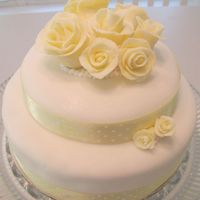 Yellow Cake   2 tier round cake. first time using fondant. fondant covered and fondant roses, real ribbon.