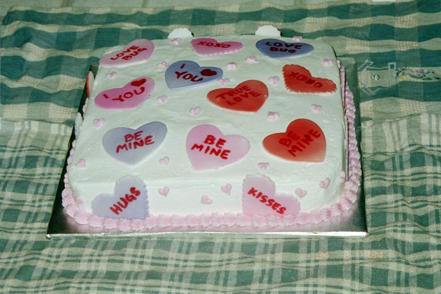 Hearts Cake Just fondant hearts with the message heart sayings written on them. Made it for a bake sale at work.