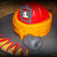 Fireman Graduation Carved cake for the helmet. 8 inch cake for bottom. Made for a Fireman's Graduation. The water is made out of sugar.