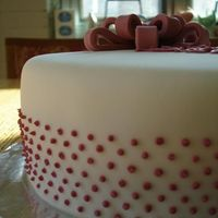 White Fondant With Pink Dots This is a white fondant covered cake with pink buttercream dots and a pink fondant bow.