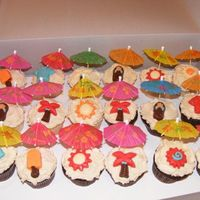 Beach Cupcakes 12 yellow and 12 chocolate with BC frosting with candy piece and paper umbrella.