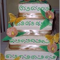 Square Wedding Cake 4 Tier wedding cake buttercream icing, gumpaste flowers, rhinestones and ribbon.