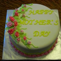 Viligrana Mother's Day Cake White Cake covered in fondant, fondant ribbon roses in 2 different colors, lime green leaves, yellow writing & scroll work on sides,...