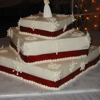 My_Snowflake2.jpg   only my second wedding cake. the bride wanted snow flakeswith red ribbon around each tier.