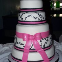 Mallory's Wedding Cake White almond cake with white fondant. Black and fuschia fondant ribbons on the bottom with fushia bow in center. The squiggles are black...