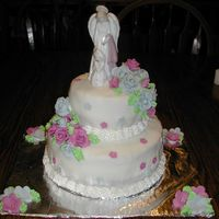 Julia's First Communion Cake This is a 2 tiered First Communion Cake. It is covered in fondant with fondant roses. The topper is ceramic. The borders and leaves are all...