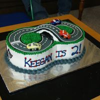Race Car Track This was 2- 8 inch cakes put together. The frosting is buttercream & the race cars on fondant. Lots of fun.
