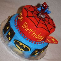 Superhero Cake A cake done with inspiration from several on this site. All buttercream with Hershey bar buildings, fondant windows and superhero logos,...