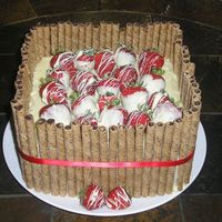 Strawberry's And Chocolate  This was made for a friends going away party at work. It's strawberry cake with white chocolate icing and fresh dipped and swirled...