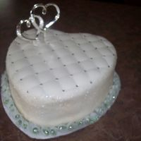 Bridal Shower cake is white with raspberry filling, covered in almond buttercream and fondant. Sides are covered in shiny sugar flakes. Made this for a...