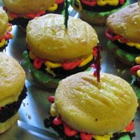 "Hamburger Cupcakes   Yellow cake ""buns"" with brownie ""burgers"". SMBC ""ketchup, mustard, and lettuce""."