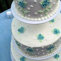 Blue Flowers Three Tiered Buttercream frosting with fondant flowers.