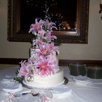 Stargazing On A Quilt  This is a 4 tier wedding cake with rhinestones on metal twisted, covered with stargazer lilies coming down the tiers. Each tier is 4 inches...