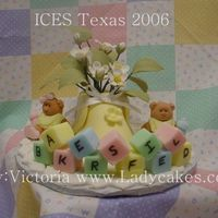 Baby Bootie With Gum Paste Flowers This is a baby Bootie filled with Gum Paste Flowers the board is a baby blanket done in patchwork cutters and the frig is done with...