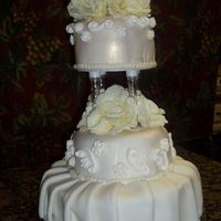 First Wedding Cake  3-tier wedding cake, round bottom tier, hexagon middle tier and round top tier. Fondant Pleats on bottom and fondant covered middle and top...