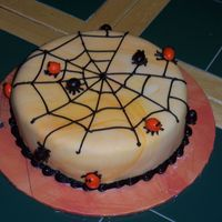 Spiders And Spider Web   I cover the cake with orange marble fondant. Pipe on the web and made the spiders out M&M.