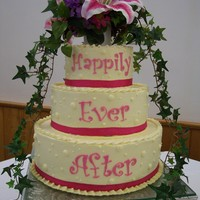 Pink Happily Ever After   Three tier cake covered with French buttercream and silk flower topper.