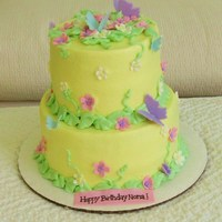 "Butterflies And Flowers 8""/6"" Buttercream covered with fondant butterflies, flowers and banner."