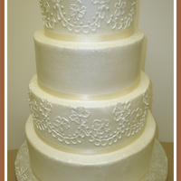 Simple But Elegant 4 tier white cake, 14, 12, 10, 8...raspberry filling, buttercream icing. Royal icing piping.