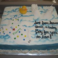 Baby Boy yellow butter cake, bc icing, airbrushed sky, fondant onies and booties, chocolate duck and bottle. The was a last minute cake. But it was...