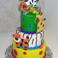 Jungle Birthday All buttercream with wooden animals and curly ribbon.