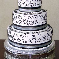 Brown Scrollwork And Ribbon   12/9/6 inch stacked rounds decorated with buttercream icing and satin ribbon.
