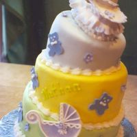 Rock -A -Bye Baby Nathan 3 tier tippy baby shower cake. Fondant icing with gumpaste cradle, baby buggy and teddy bears (complete with sleeping gumpaste baby!).
