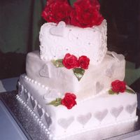 My Valentine Love 3 tier, square Valentine's Day wedding cake. Middle layer embossed and entirely dusted with Satin Silver petal dust. Fondant, Satin...