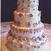 Purple Romance  4 tier wedding cake with a different design on each layer. Fondant covered and embossed board, fondant covered cake and gum paste flowers,...