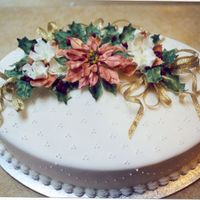 Poinsettia Cake  Oval cake, fondant covered with suisse dot design. Bronze Poinsettia, white Christmas roses, Holly leaves and berries - all made from...