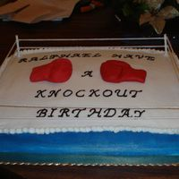 "Boxing Ring 12x16 cake with lollipop sticks and yarn to make the ""ropes of the rings"" the gloves are hand molded gumpaste. I forgot to add..."