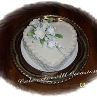 White Lily Cake Heart shaped cake decorated with white lily spray , basketweave on the sides, reverse shall border.