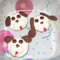 Puppy Cupcakes I made these for my DD's 9th Birthday. I got the idea for these from the Cupcake Fun book. They are BC frosted with M&M eyes, a...