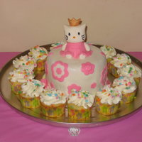 "Hello Kitty Cake With Cupcakes This is 2 6"" rounds covered in MMF with a fondant Hello Kitty on top. My daughter wanted it to be a princes Hello Kitty so that's..."