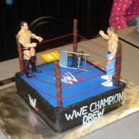 Wrestling WWE cake for my neighbor. I used chocolate dipped pretzel rods for the posts. I wish I had pre-measured them and cut them down a little but...