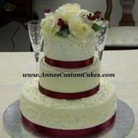 "Bride On A Budget   All buttercream, 12"", 8"", and 6"". Satin ribbon and silk flowers. Silver dragees to accentuate scrollwork and second tier."