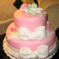 Pink Baby Shower Cake With Ribbons And Rattle cake covered in fondant, all decorations are fondant