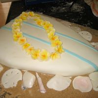 Surfboard With Plumeria And Seashells cake is covered with fondant and surrounded with brown sugar sand. plumeria and shells are gumpaste