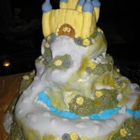 Enchanted Castle Cake Cake is covered in fondant. A cobblestone walk on the mountainside over a river to the castle.