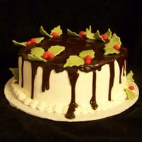 Christmas Holly With Ganache Red Velvet cake with buttercream & ganache. Decorated with fondant accents.