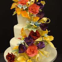 Cascading Flowers 3 tiers wedding cake covered with off white fondant. All flowers are made from gumpaste.