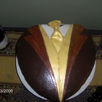 Tuxedo Triple chocolate. Chc. cake, chc. b/c, bathed w/ chc. ganache. Fondant accents w/ gold luster. This is the after pic. 10' heart pan