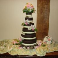 Chocolate Wedding Cake  6 tiers covered in chocolate fondant floating, using a 6 tier acrylic stand. Placed over river rocks and decorated with orchids and varies...