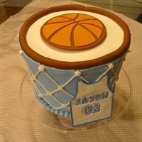 "Basketball Hoop Cake Cake frosted in buttercream. Jersey is made from royal flow icing. Basketball and ""rim"" is made from fondant. The cake is four 9&..."