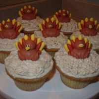 Turkey Cupcakes Turkeys are piped out of royal icing and sit on cinnamon cream cheese frosting.