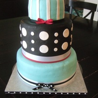 "Black, White, Teal And Red Wedding Cake 12"", 9"", and 6"". Top and bottom cakes are white cake with raspberry cream cheese filling and covered in MMF. Middle layer..."