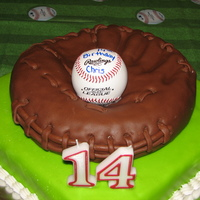 Son's 14Th Birthday Cake   Glove is made out of a round cake, carved covered in chocolate fondant. Base is vanilla pound cake covered in marshmellow fondant.